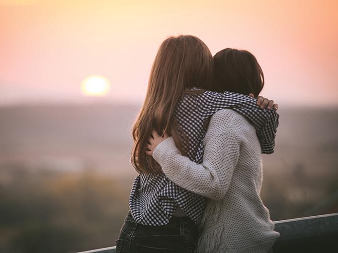 Adorable friends at golden autumn sunset.