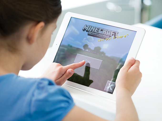 Little girl playing Minecraft on Apple iPad Air