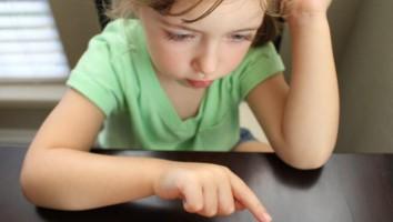kid looking at tablet