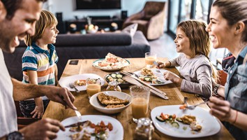 Young happy family talking while having lunch at dining table.