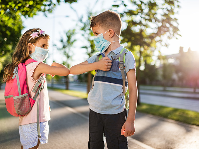Two school children using elbow bump as an alternative handshake outdoors in nature